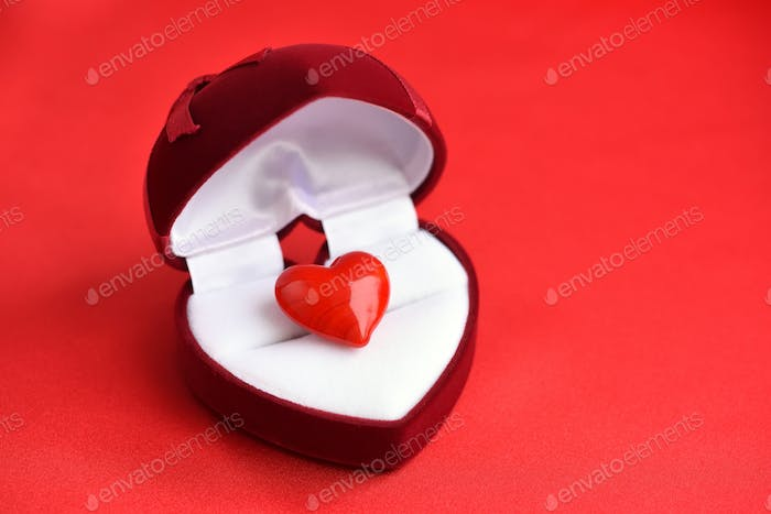 Thumbnail for Open heart-shaped gift box with glass heart on red satin fabric