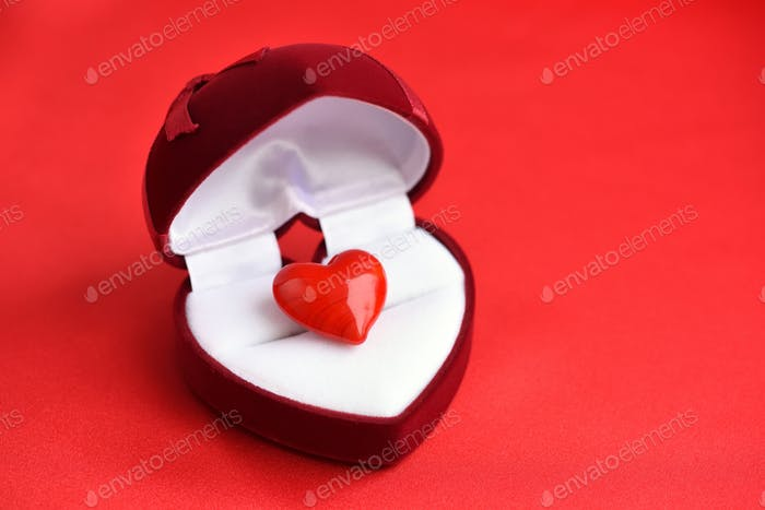 Open heart-shaped gift box with glass heart on red satin fabric
