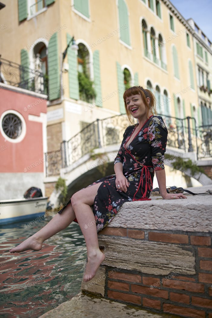 Caucasian redhead woman with floral dress sitting near a canal in Venice