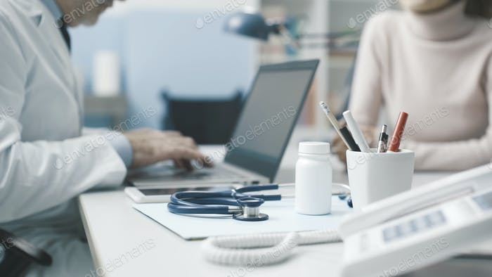 Doctor talking with a patient and typing with his laptop