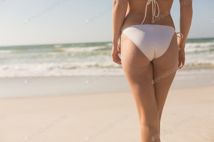 Mid section of young Caucasian woman in bikini standing on beach. It is sunny day