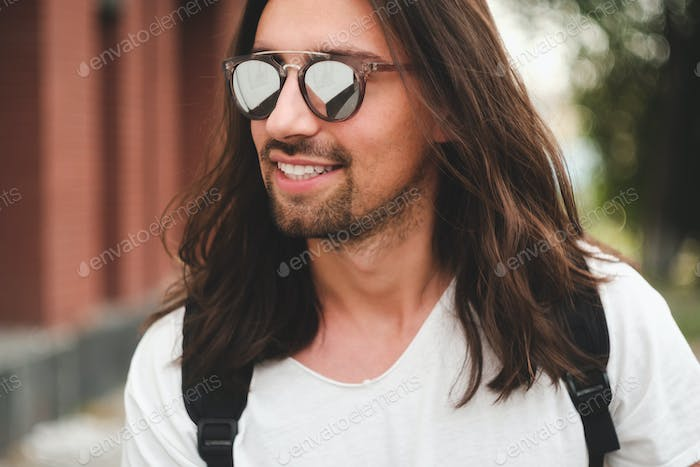 Portrait attractive man with sunglasses on urban background smil