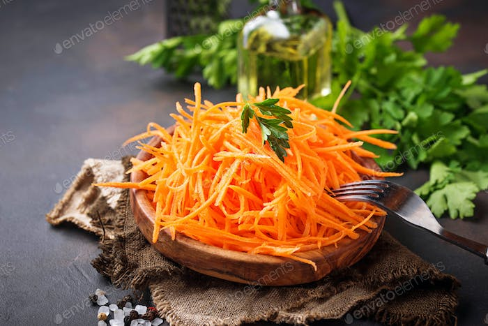 Fresh grated carrot on wooden plate