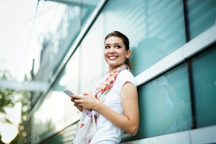 Beautiful young woman messaging on the smartphone. Social network concept