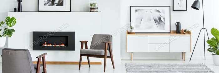 White living room interior with grey armchairs, simple posters,