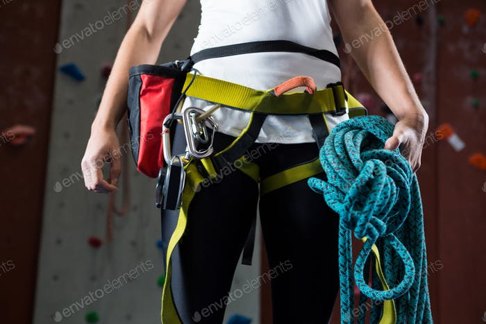 Woman in safety harness holding rope in fitness studio
