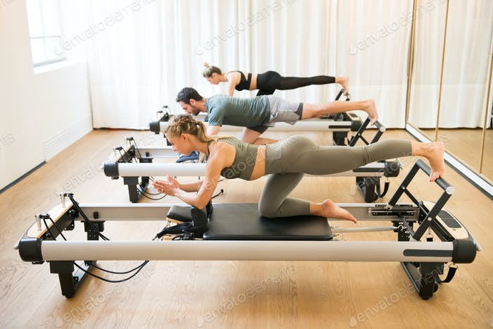 Friends doing pilates kneeling glutes exercises