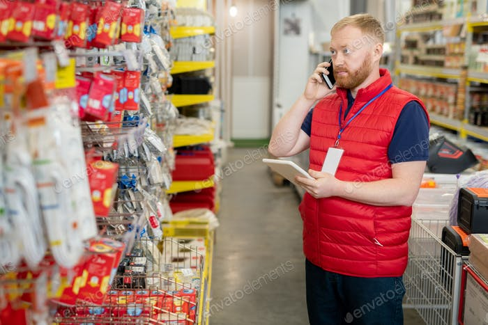 Shop assistant consulting clients on mobile phone