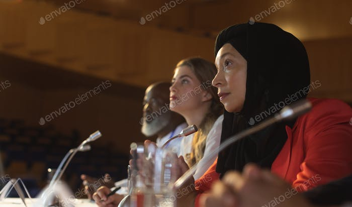 SIde view of mixed race business executive looking and listening while sitting in the auditorium