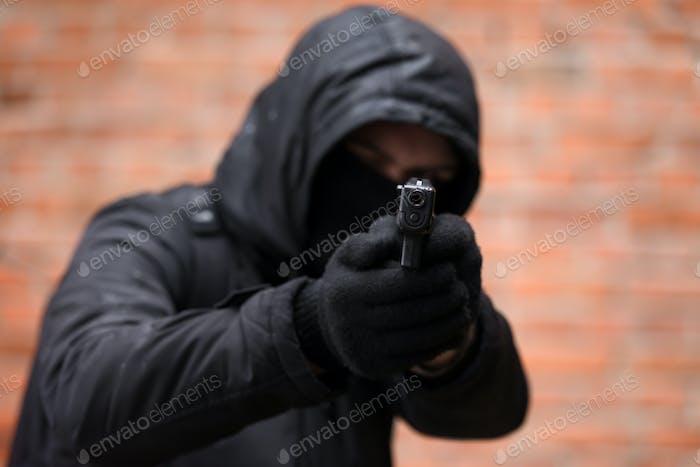 Mann in schwarzer Maske mit Handfeuerwaffe