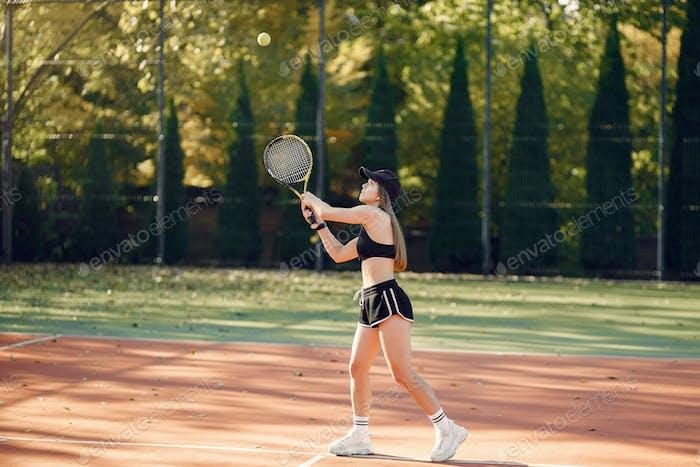 Schöne und stilvolle Mädchen auf dem Tennisplatz