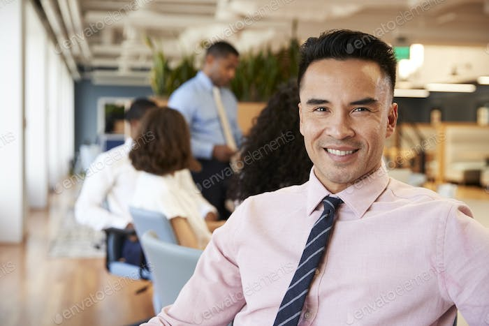 Portrait Of Businessman In Modern Office With Colleagues Meeting Around Table In Background