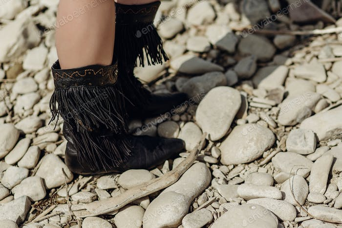 fringe boot. stylish hipster boho traveler woman wearing suede boots on river beach