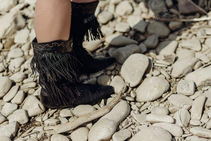 Fransenstiefel. stilvolle hipster boho reisende frau tragen wildleder stiefel am fluss strand