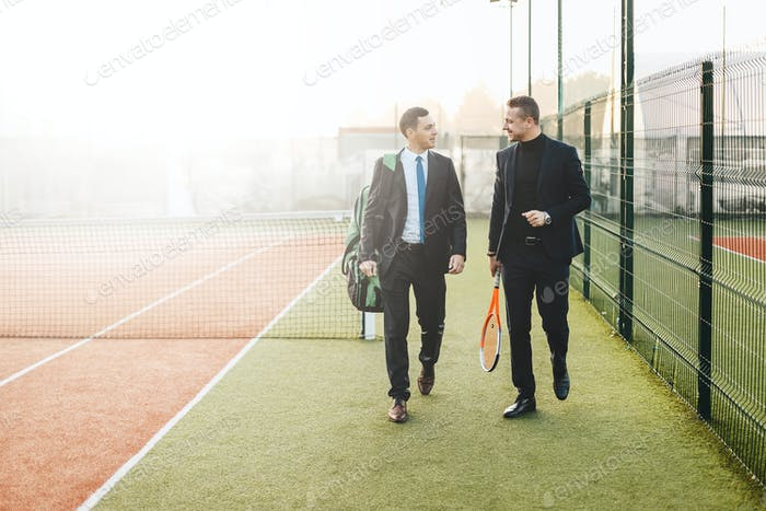Two businessmen walking and communicating