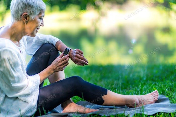 Seniorin sitzt am Wasser, Einstellung ihrer Meditation Smart-Watch-app