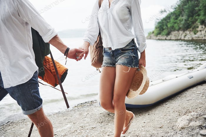 Cute young and couple on river background. A guy and a girl with backpacks are traveling by boat