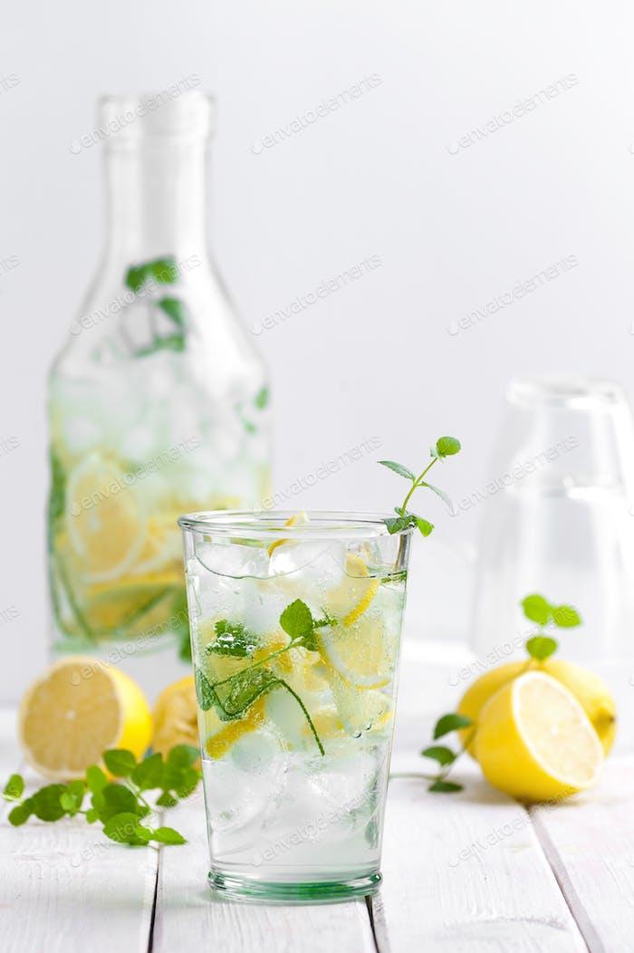 Limonade in einer Glasschale auf einem weißen Holztisch.