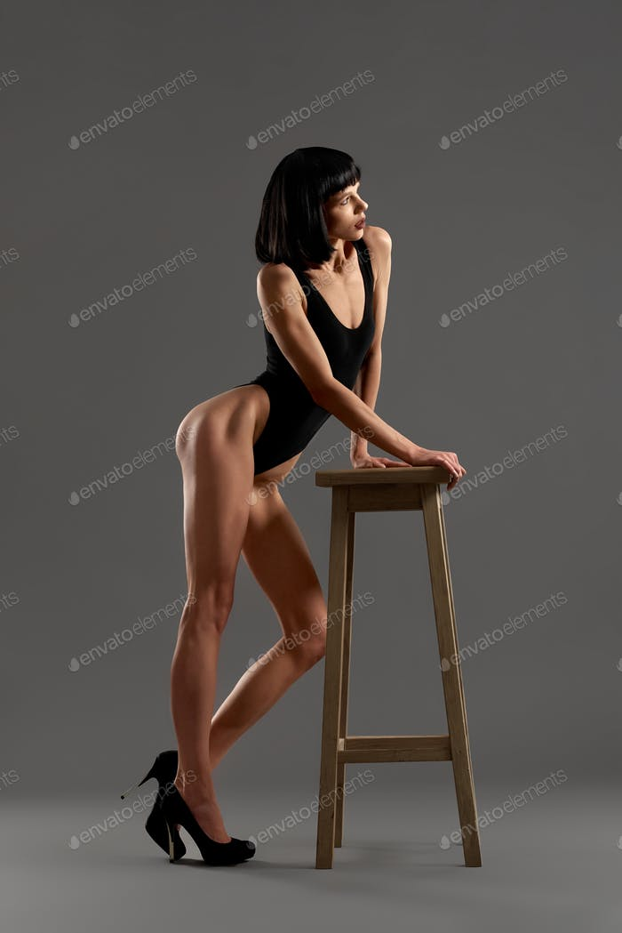 Brunette in high heel shoes leaning on chair