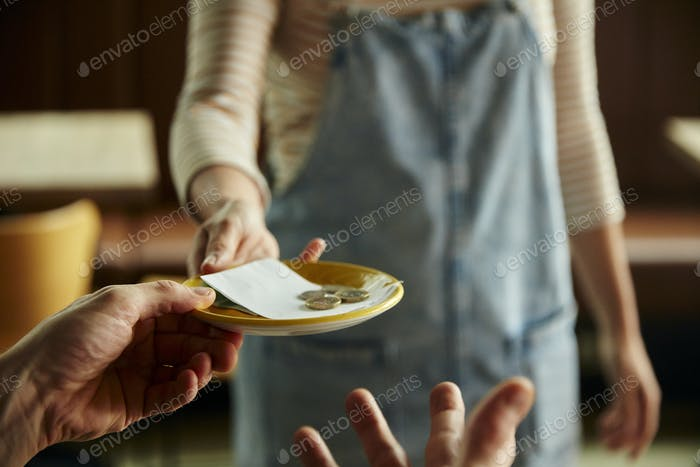 Woman holding out a plate with a cafe bill and coins.