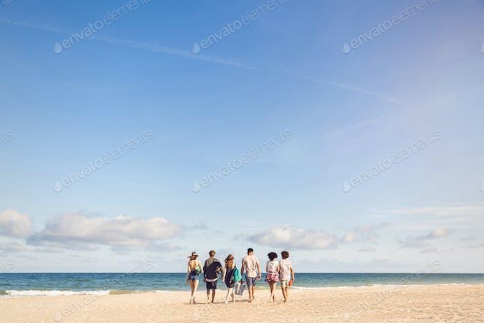Gente caminando en la Playa llevando una caja de refrigeración