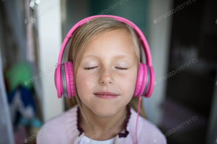 Girl listening to music on headphones at home