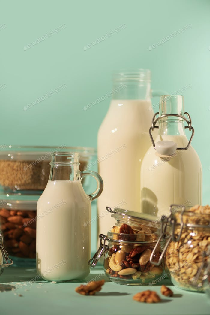 Glass bottles of vegan plant milk and almonds, nuts, coconut, hemp seed milk on blue background