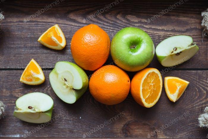 Manzana y naranja en la bandeja de De madera