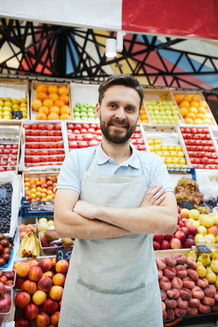 Content handsome retailer with beard against fresh food shelves