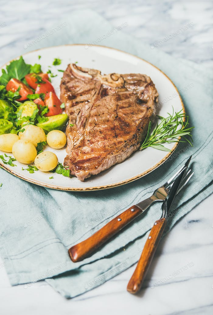 Cooked beef tbone steak with vegetables and rosemary in plate
