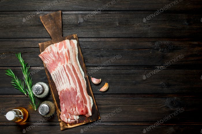 Raw bacon with rosemary and spices.