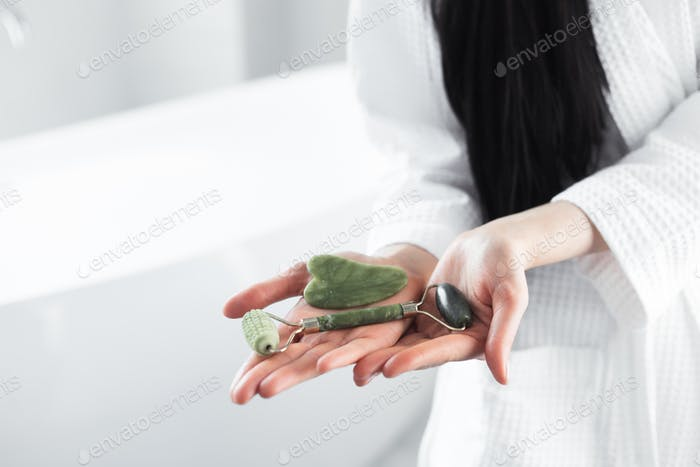 Jade green roller and gua sha massage scraper in woman hands