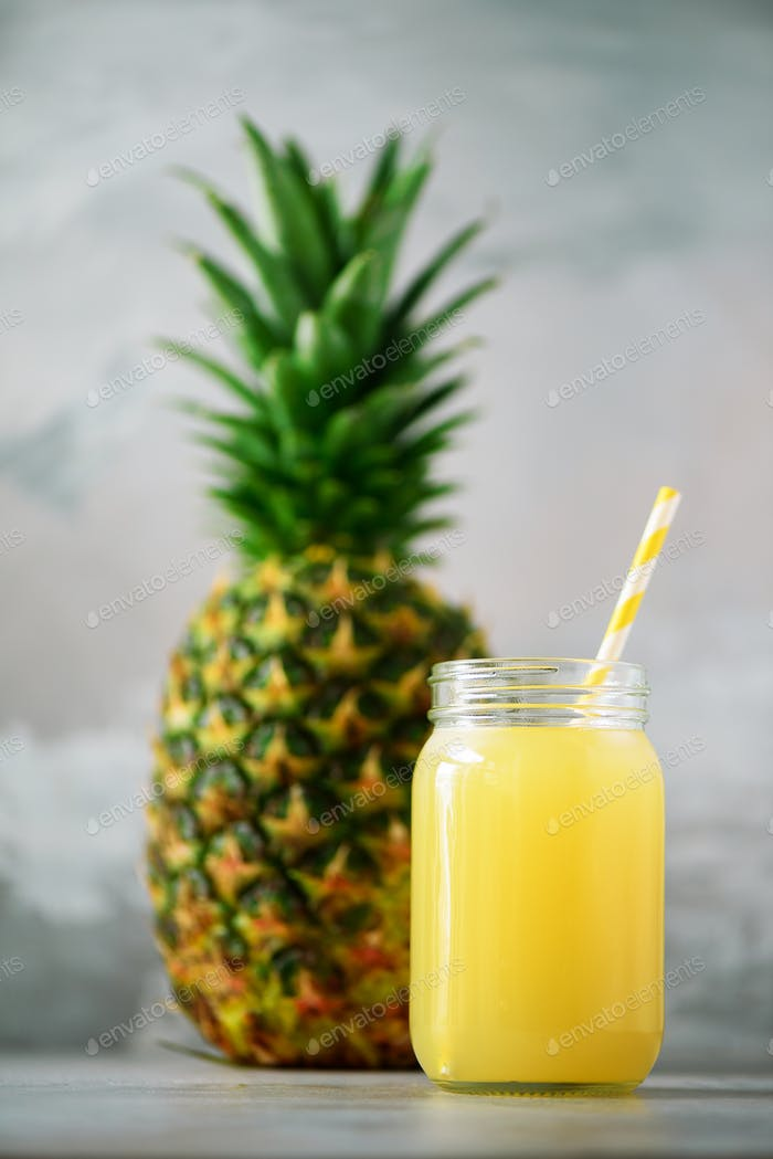 Glass jar of pineapple smoothie and whole fruit on gray background. Copy space. Summer, holiday