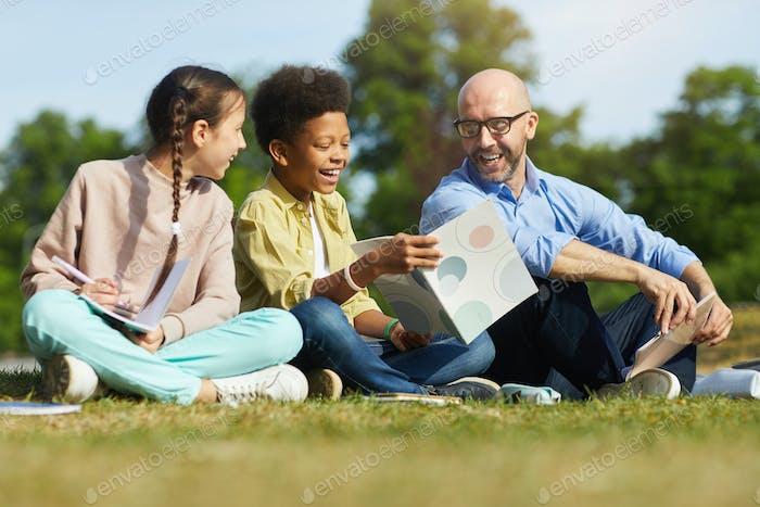 Lächelnde Kinder mit Lehrer im Freien