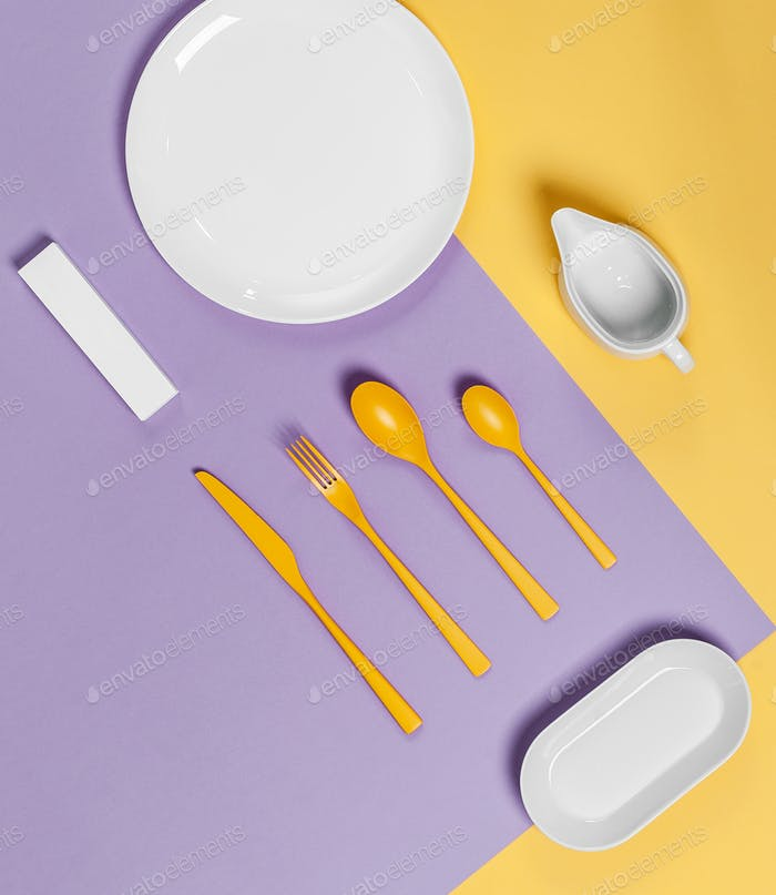 White tableware and yellow cutlery on a yellow-violet pastel bac