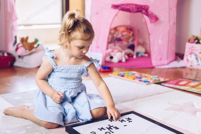 Girl playing in her room with a letter board written my brother is coming