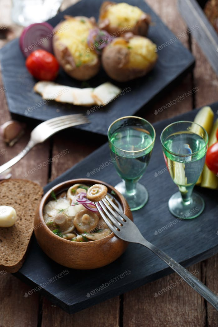 Pickled tomatoes, cucumbers, mushrooms and onion on wooden background with fork and shots of vodka.