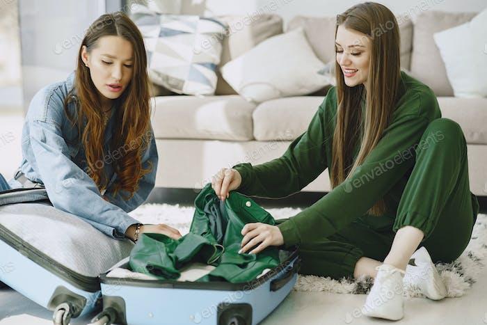 Les femmes préparent valise de voyage à la maison