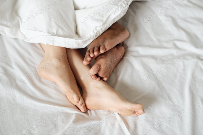 Bare feet of multiracial females lying in bed