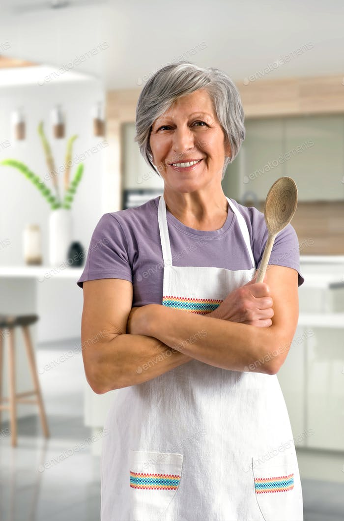 Happy friendly senior woman baking in the kitchen