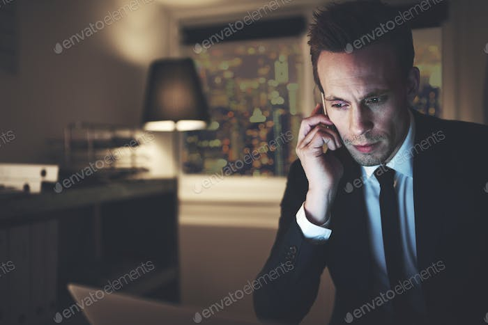 The finance adviser with phone browsing laptop