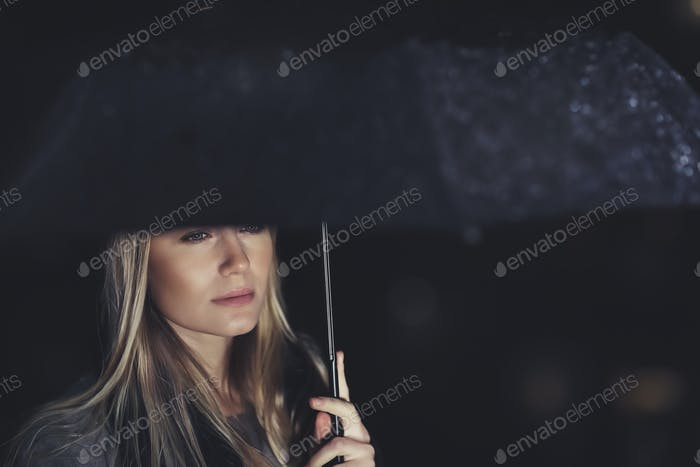Beautiful sad woman under the rain