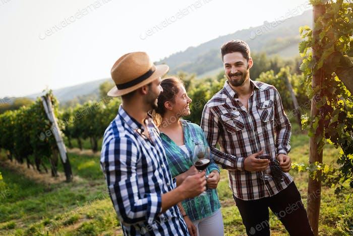 People sampling and tasting wines in vineyard