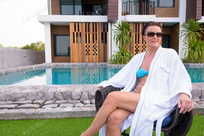 Mature beautiful Scandinavian tourist woman sitting near swimming pool in resort