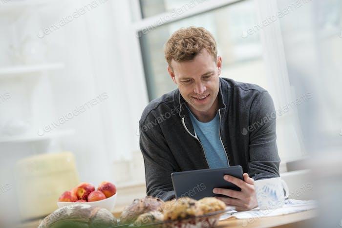 Ein Mann in einem Sweatshirt mit einem digitalen Pad. Lehnen sich auf eine Frühstücksbar.