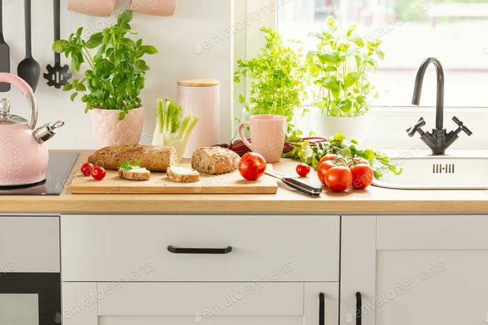 Close-up of bread, tomatoes and plants on a countertop in a kitc