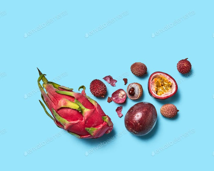 Juicy halves, whole peel and fruit lychee passion fruit and pitahaya on a blue background with space