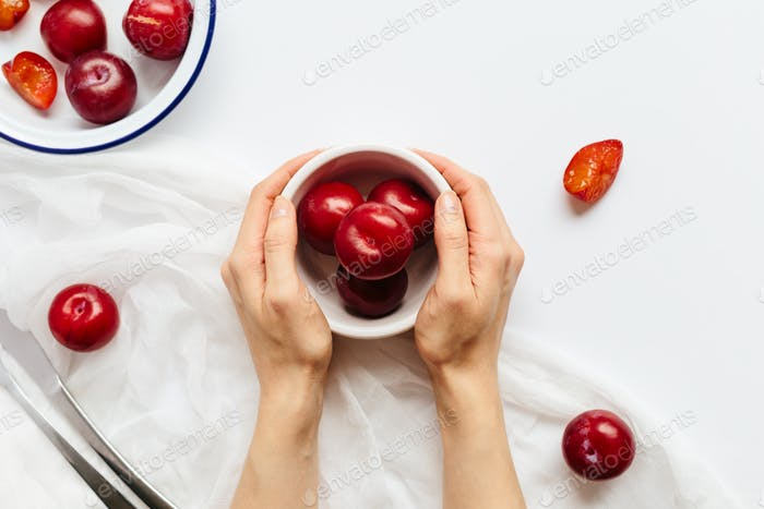 Female Hands Holding Bowl of Plums