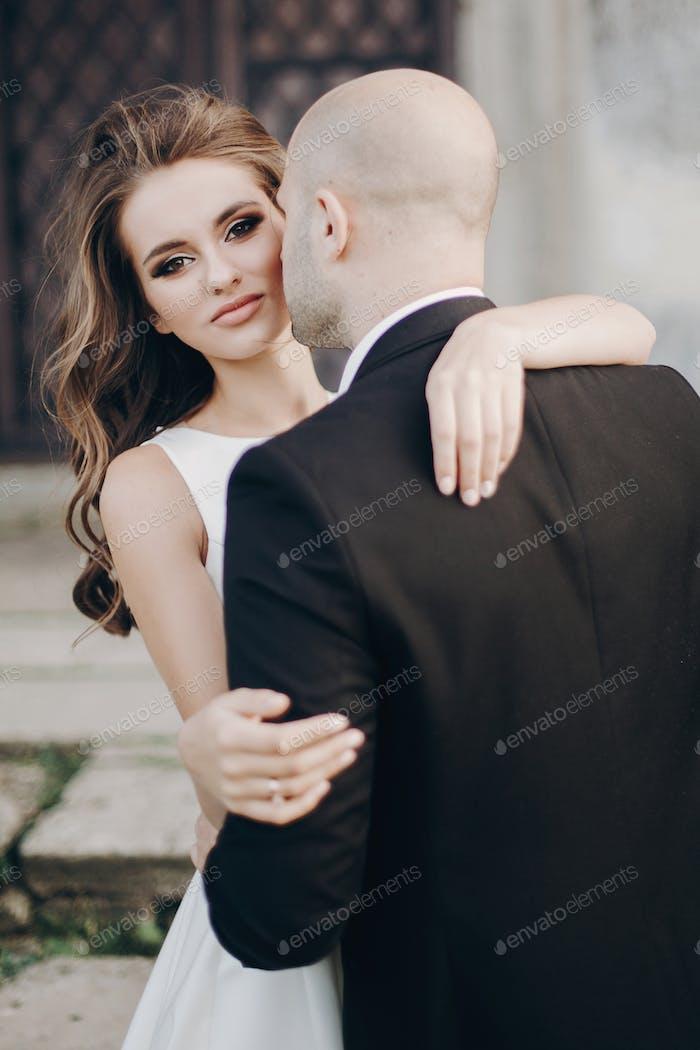 Stilvolle Hochzeitspaar sanft umarmt und lächelnd