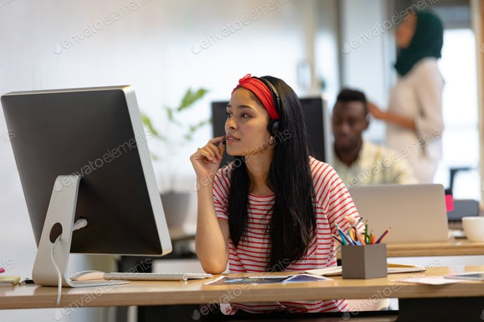 Front view of Mixed-race female customer service executive talking on headset in a modern office